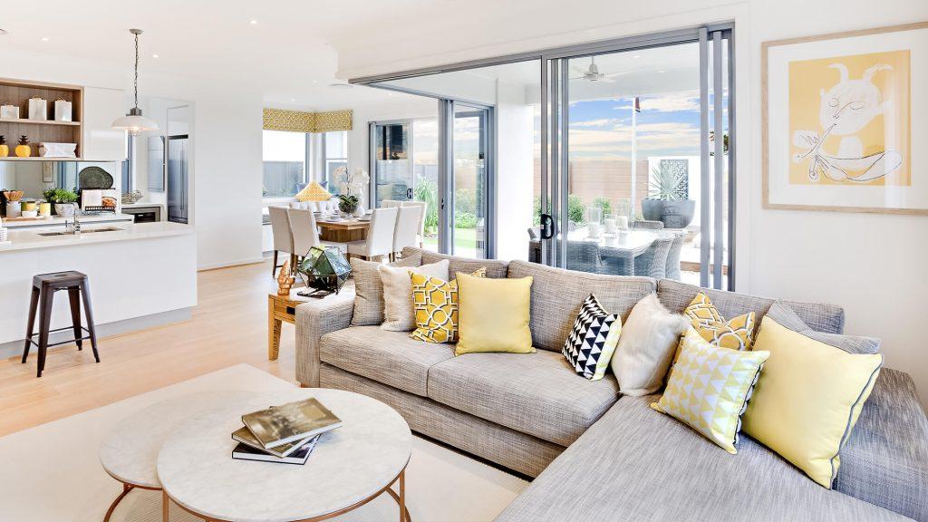 Wohnzimmer eines Hauses, das zur Küche, zum Esszimmer und zur Terrasse hin offen ist
