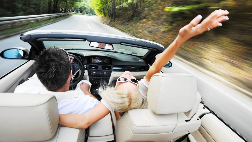 Junges Paar auf der Suche nach einem Cabrio auf einer Landstraße
