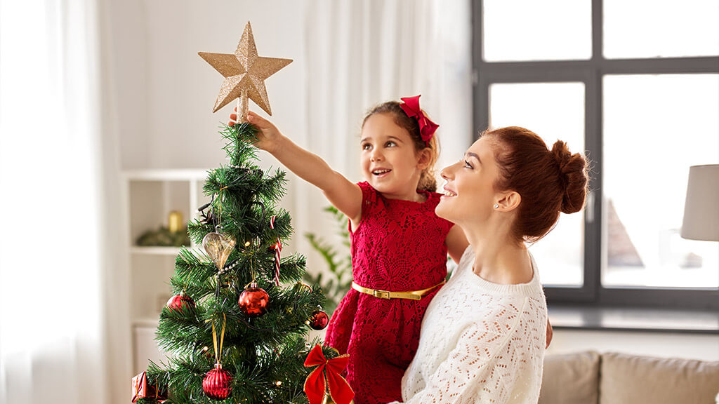 Mother and her little girl decorating the Christmas tree