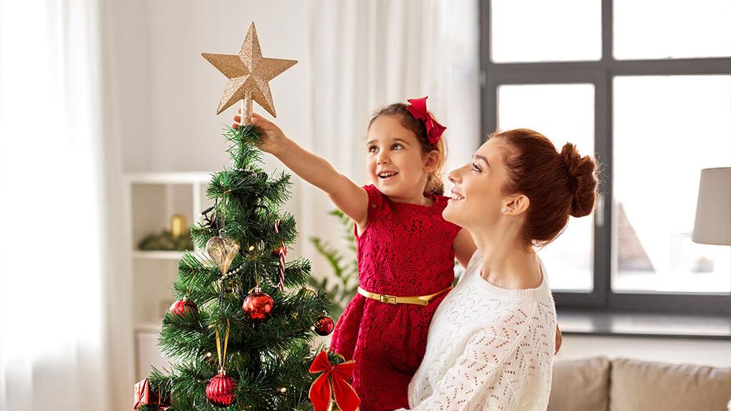 Maman et sa petite fille décorant le sapin de Noël