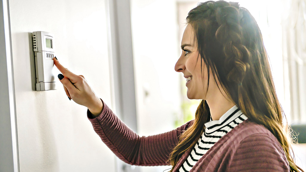 Young woman adjusting her heating thermostat.