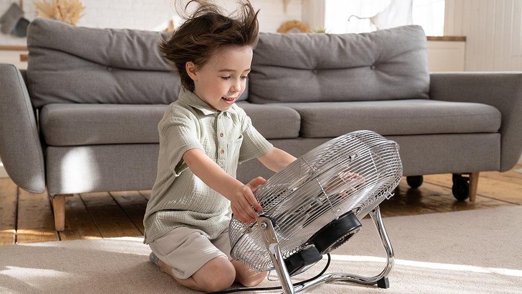 Petit garçon qui se rafraichît avec un ventilateur dans son salon
