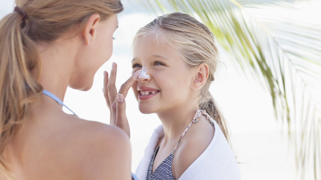 Une maman qui met de la crème solaire à  son enfant à la plage