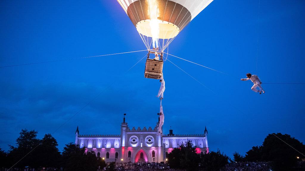 spectacle de nuit avec des acrobates aériens et une montgolfière