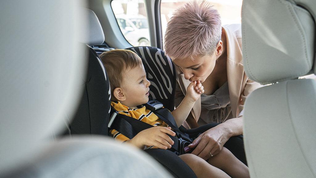 une maman qui attache son bébé dans un siège-auto