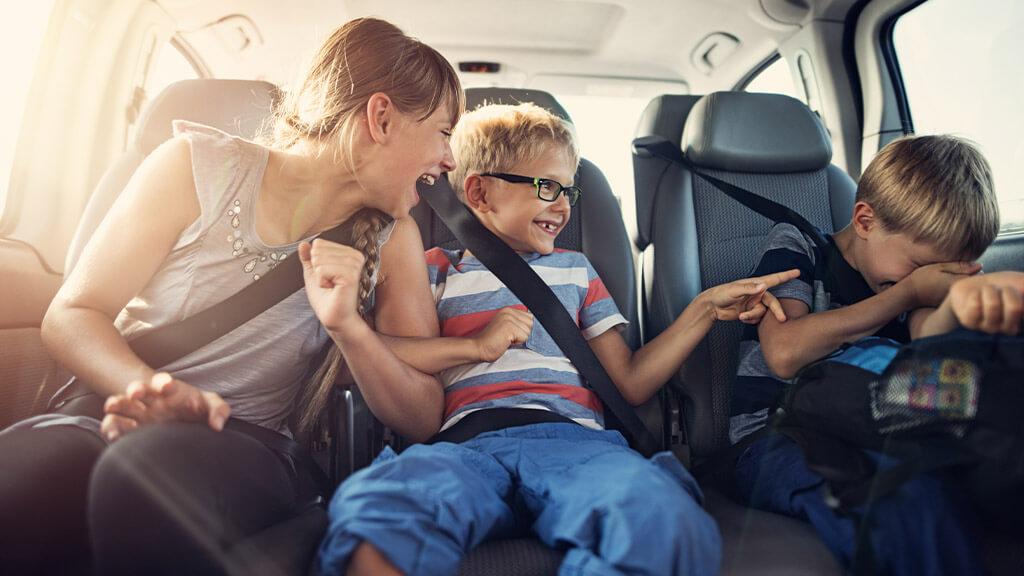 trois enfants qui s'amusent à l'arrière d'une voiture